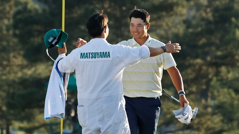 Hideki Matsuyama celebrates on the No. 18 green with caddie Shota Hayafuji after winning the 2021 Masters.