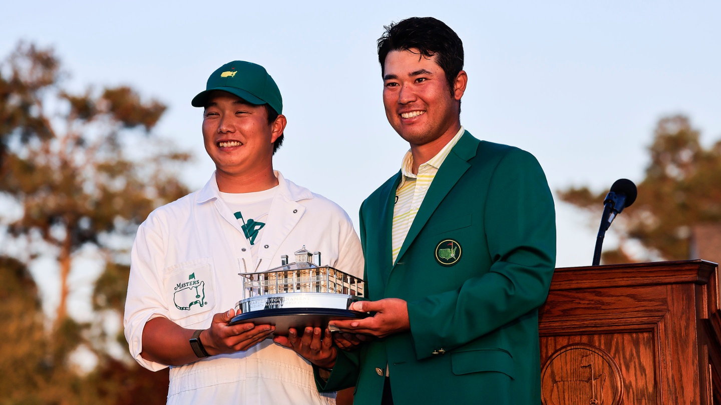 Hideki Matsuyama holds the Masters Tournament Trophy with his caddie Shota Hayafuji after winning the 2021 Masters. image