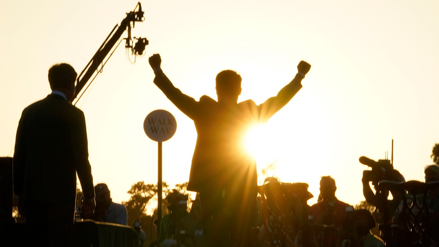 Hideki Matsuyama raises his arms skyward after being awarded the Green Jacket for winning the 2021 Masters. image