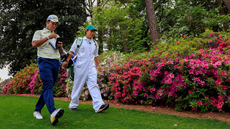 Hideki Matsuyama and caddie Shota Hayafuji walk toward the No. 6 greenduring the final round of the 2021 Masters. image