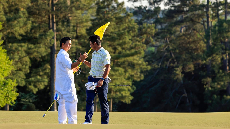 Hideki Matsuyama celebrates with caddie Shota Hayafuji on the No. 18 green after winning the 2021 Masters. image